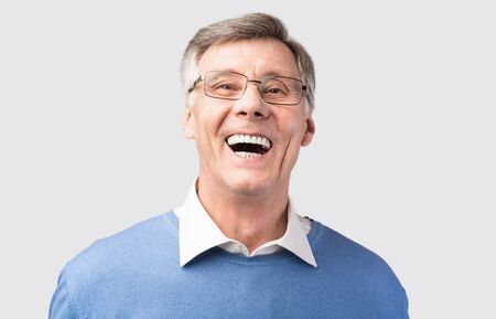 Lol. Elderly Man Laughing Out Loud Looking At Camera Posing In Studio Over Gray Background.