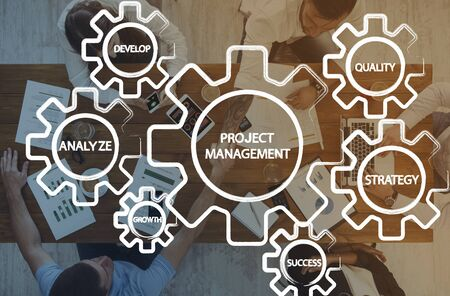 White gears with project management features over top view of business team working at office