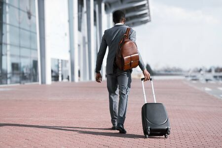 Business Trip Concept. Black Businessman With Travel Suitcase And Backpack Walking Back To Camera Leaving Airport. Copy Space