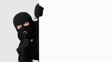Keep Silence. Masked criminal peeking out white blank board, making hush sign, isolated on white studio wall