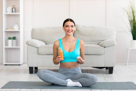 Healthy Life. Fitness Woman Holding Bottle Of Fruit Juice Smiling To Camera Sitting On Rolling Mat During Training At Home