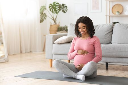Beautiful happy pregnant african woman hugging her tummy, sitting on sport mat, enjoying her pregnancy, free space