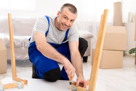 Happy Repairman Assembling Furniture Installing Table After Transportation In New Home, Smiling To Camera Indoor. Furnishing And Assembly Services.
