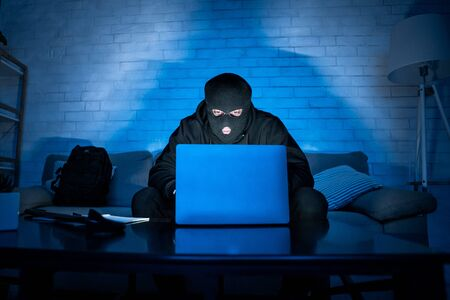 Private Information Security Concept. Masked hacker using pc, sitting in the dark on couch, stealing big data