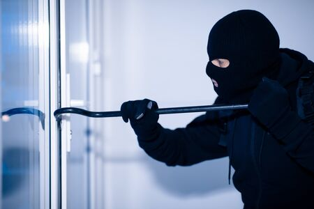 Home Security Concept. Burglar in Action Trying To Break Into the House Using Crowbar, Side View Banque d'images