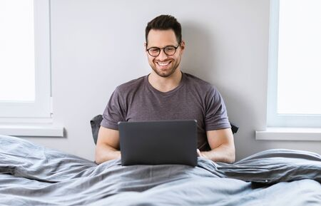 Happy Man Working On Laptop Computer Online Sitting In Bed At Home. Freelance And Distant Work Concept.