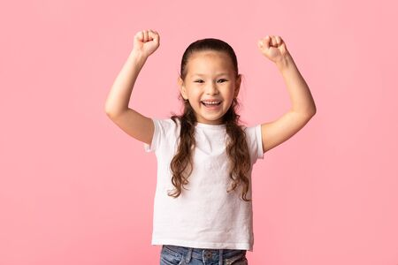 Excited asian child making winner gesture, raising fists up, isolated over pastel pink studio wall, copy space