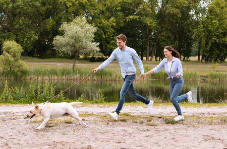 Active Pet Concept. Laughing couple chasing their running dog in park near lake, copy space, full length