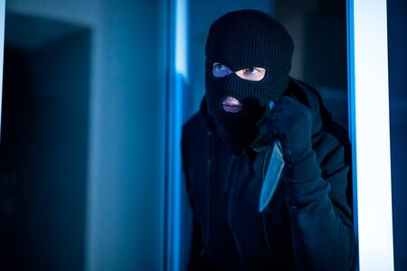 Homicide Concept. Murder in black balaclava breaking into house at night, holding knife in the dark, ready to kill