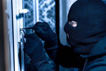 Vandalism Concept. Side view closeup portrait of unrecognizable thief in black balaclava unlocking door with picklock Stockfoto