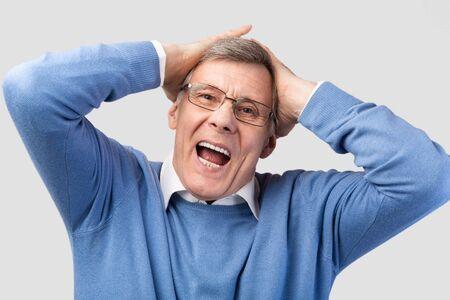 Emotional Senior Man Shouting Touching Head Posing On Gray Studio Background. Oh, No Concept 免版税图像