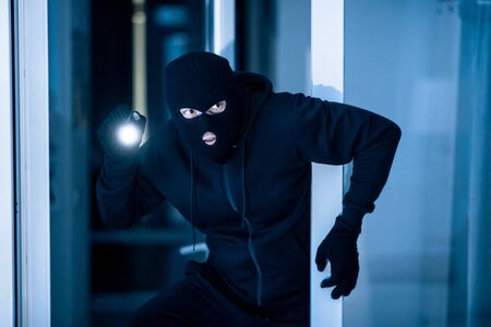 Stealthy criminal wearing black balaclava sneaking into house through window or glass door, using torch at night