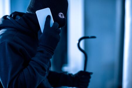 Threatening Concept. Thief wearing black balaclava talking on smart phone and holding crowbar at night