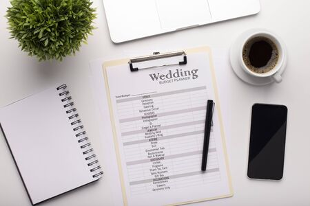 Office workplace with wedding planner and items to do before event, cellphone with blank screen