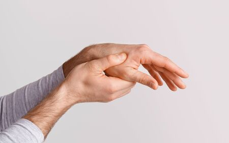 Fracture, injury or pain in arm. Man presses one hand with other isolated on gray background, studio shot, close up Foto de archivo