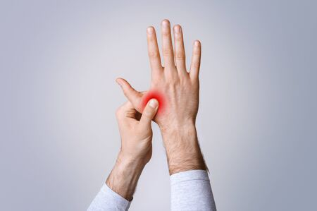 Inflammation in muscles and joints. Man holds to highlighted red hand isolated on gray background, studio shot