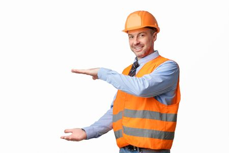 Cheerful Construction Worker Holding Invisible Building Gesturing With Hands Posing On White Studio Background. Free Space