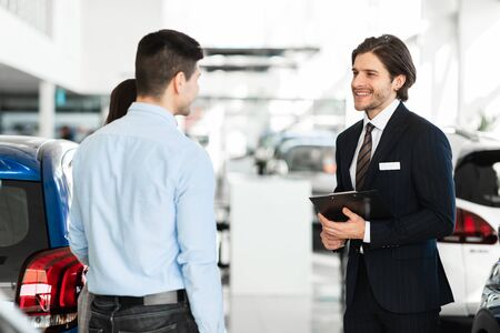 Car Sale. Handsome salesperson holding clipboard talking to young family, showing vehicles