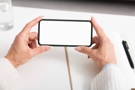 Watch videos and lessons online. Adult woman hands holds smartphone with blank screen on white table background Archivio Fotografico