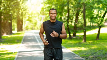 Smiling black guy with mobile device and earphones jogging at park on sunny day, panorama