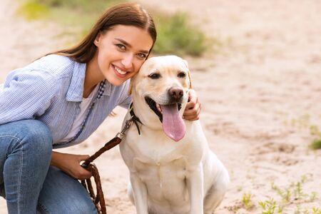 Haustiere lieben Konzept. Schönes Mädchen posiert vor der Kamera mit ihrem süßen Hund beim Spaziergang, Kopierraum, unscharfer Hintergrund