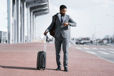 Delayed Flight. African American Businessman Checking Time On Wristwatch Standing With Suitcase At Airport Outside. Free Space Zdjęcie Seryjne