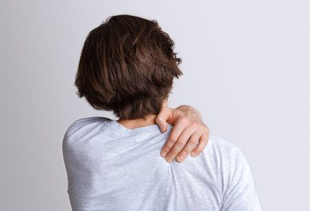 Pain in back and shoulder from working at computer. Man presses his hand to sore spot, isolated on gray background, studio shot