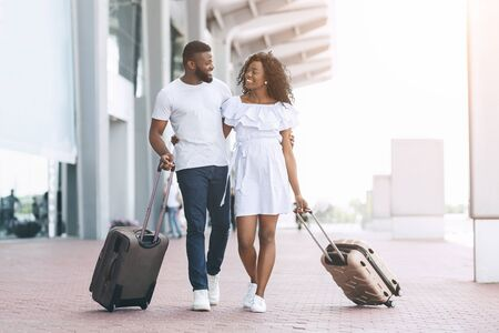 Travel Together. Portrait Of Happy Loving Black Couple Walking With Suitcases Near Airport Building
