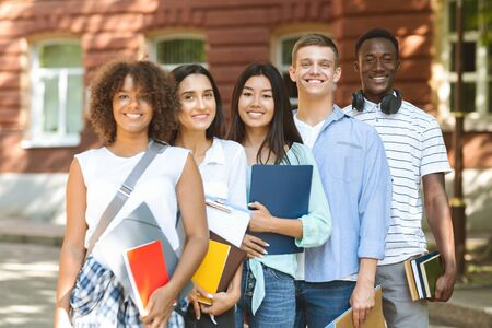 College Community. Group of smiling multi-ethnic students posing at campus, holding workbooks and smiling at camera