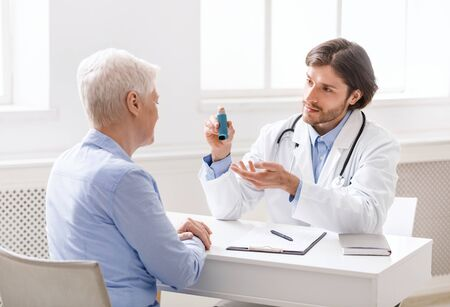 Doctor explaining pills schedule to senior patient during appointment at clinic