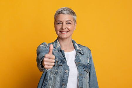 I Recommend. Friendly Middle-Aged Woman Gesturing Thumb Up At Camera, Wearing Stylish Denim Jacket, Posing Over Yellow Background, Free Space