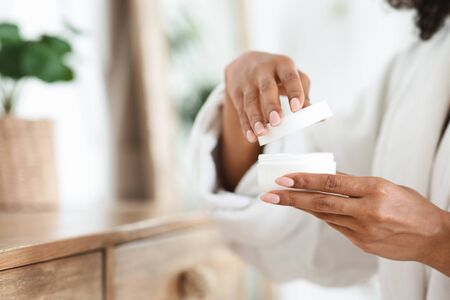 Unrecognizable african woman opening jar of skin cream, ready for daily beauty routine after shower, closeup