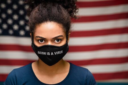 Discrimination infection. Black woman wearing protective mask with Racism is a Virus text, USA flag on background