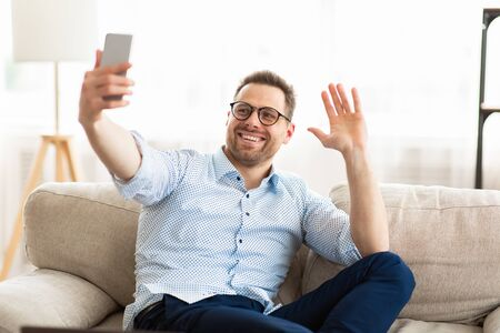 Happy adult man in specs and shirt holding phone and recording video or making call, waving at camera, free space Banco de Imagens - 150107476