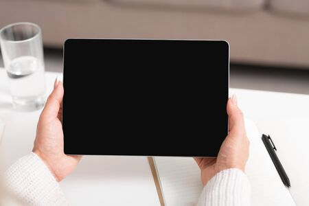 Communication with client and video call. Mature woman hands holding tablet with blank screen, sitting at table at workplace