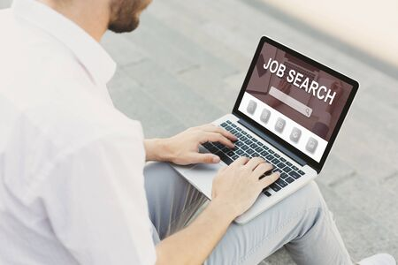 Looking For A Job. Back view over the shoulder of man using laptop with vacancies website on monitor, typing on keyboard