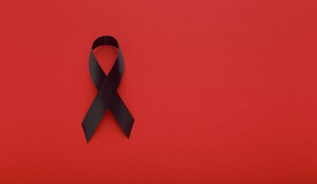 AIDS Black Awareness Realistic Ribbon isolated on red background. Drugs symbol, panorama, copy space