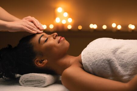 Indian spa massage in romantic atmosphere for black woman, spa salon lighted with candles interior