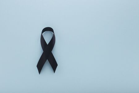 Blue background with Melanoma Cancer Awareness Realistic Black Ribbon, copy space