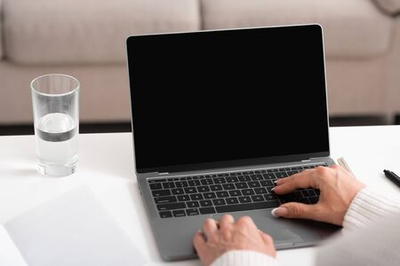 Search in internet and work at home. Female hands typing on laptop with blank screen