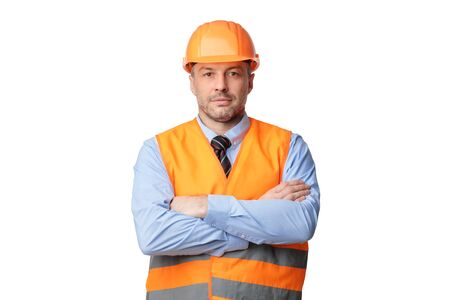 Construction Worker. Serious Builder Man Posing Crossing Hands Looking At Camera Standing Over White Background. Studio Shot