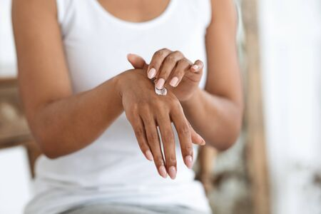 Recovery Hand Cream. African American Woman Applying Rich Lotion On Her Skin, Cropped Image