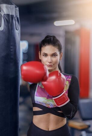 Young female boxer in gloves punching ball at sports club