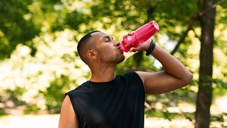Stay hydrated. Sporty black guy drinking water from plastic bottle after his training at park. Panorama Zdjęcie Seryjne