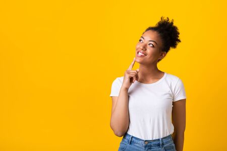 I Think. Dreamy african woman looking up, touching her chin with finger, isolated over yellow studio wall, copyspace