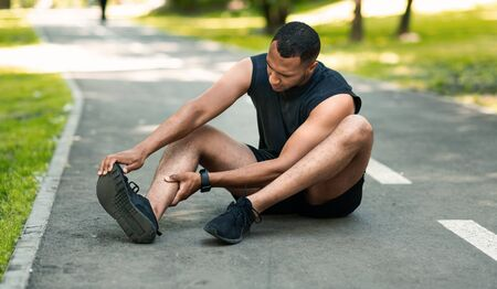 Sports injury. African American runner sitting on jogging track and feeling pain in his ankle, panorama Banque d'images