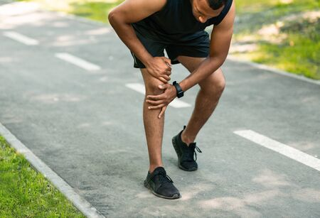 African American jogger suffering from pain in his knee during morning run at park Banque d'images