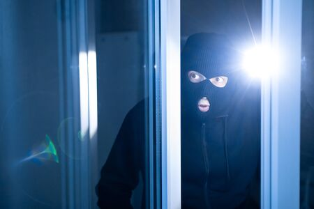 Robbery Concept. Aware masked villain lurking into house through window or glass door, using torch in the dark