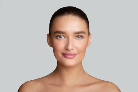 Skincare Concept. Beautiful face of healthy woman model with clear skin, isolated over gray studio wall, copy space