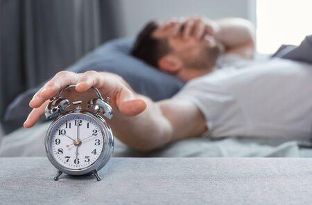 Bad Sleep. Sleepy Man Turning Off Alarm-Clock Lying Waking Up In Bed At Home. Shallow Depth, Selective Focus Reklamní fotografie